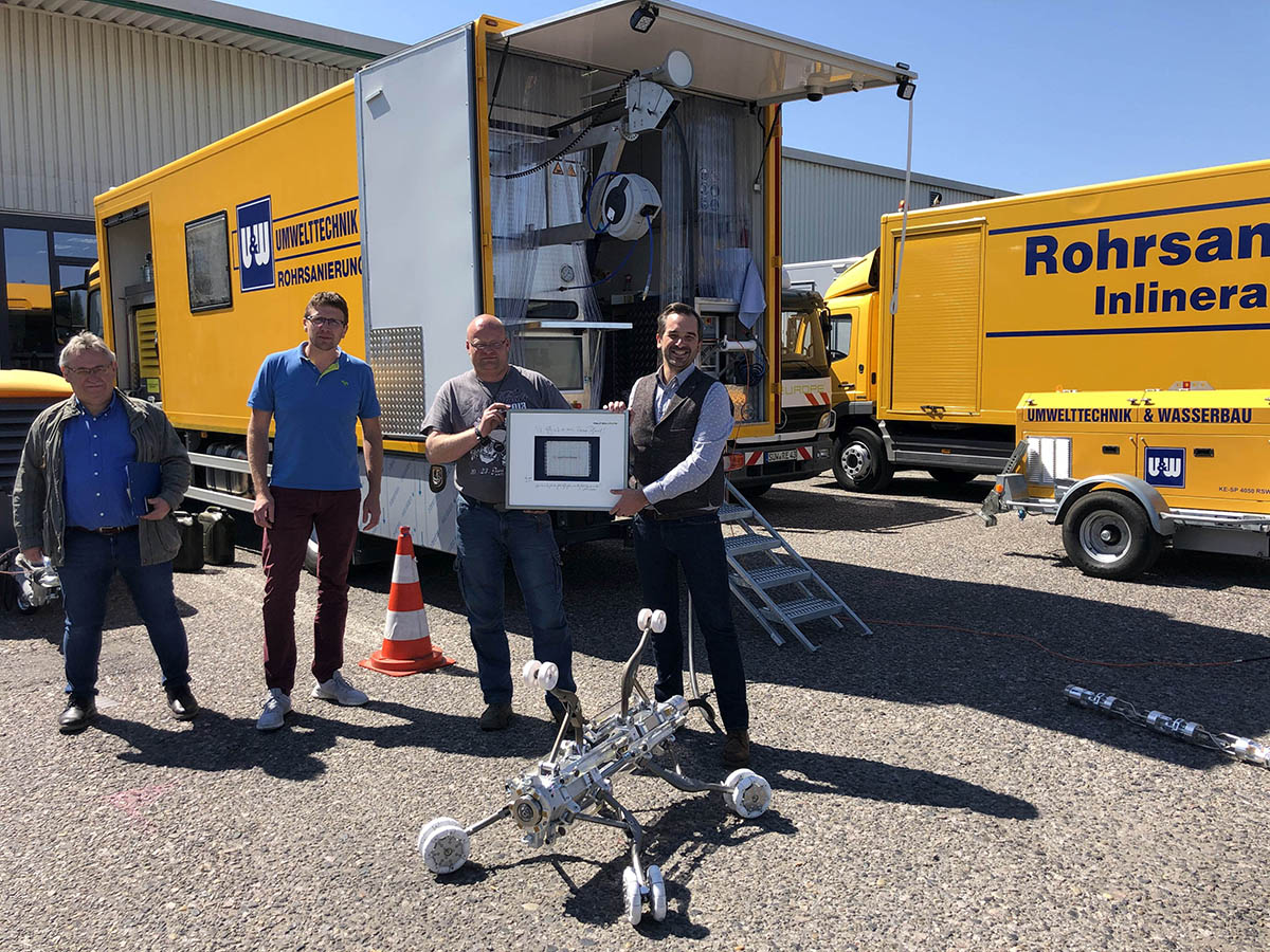 Handover of the new REE4000 Professional with battery-hybrid technology to the company U+W Umwelttechnik und Wasserbau. Left to right in the photo: U + W's MTA director Andreas Ludwig, branch manager Christoph Dorfmann, machine operator Christian Maus and RELINEEUROPE's Philipp Martin - Photo: RELINEEUROPE